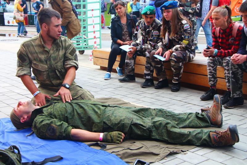Представитель военно-патриотического тренировочного центра «ВОЕВОДА-ДОСААФ» объясняет юным бойцам азы оказания первой помощи.